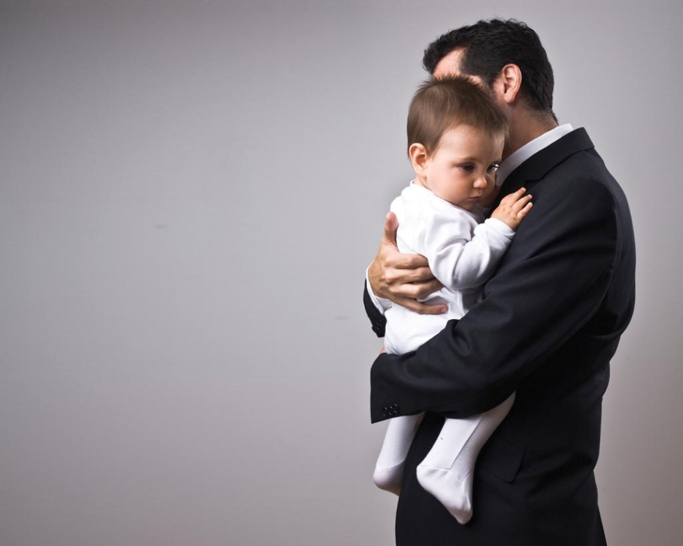 stock-photo-6538700-man-wearing-suit-holding-a-baby 2